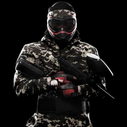 Heavily armed masked paintball soldier isolated on black background. Ad concept. Copy space.